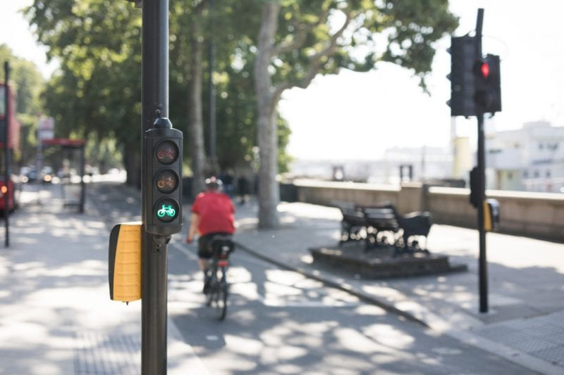 View of a traffic light button with a cycle bike lane and cyclist blurred in the background on a bright summer day in London.