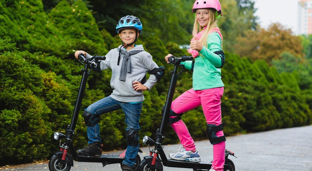 kids with electric scooters and safety equipment