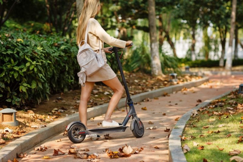 Woman riding on electric scooter in the park