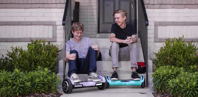 two kids sitting on porch smiling with their hoverboards