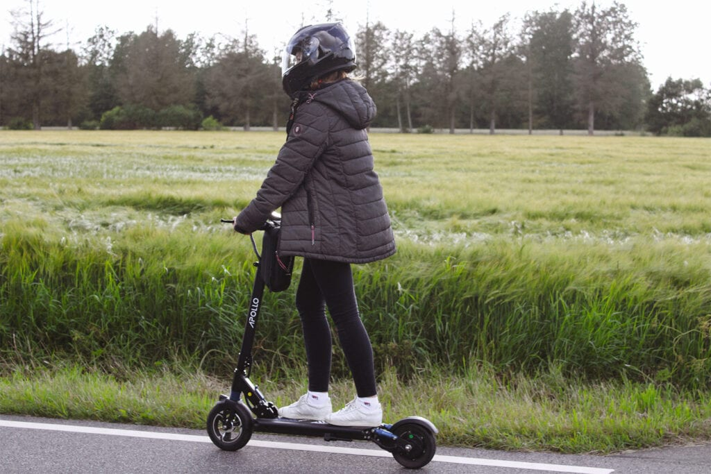 Girl riding an electric scooter using a motorcycle helmet