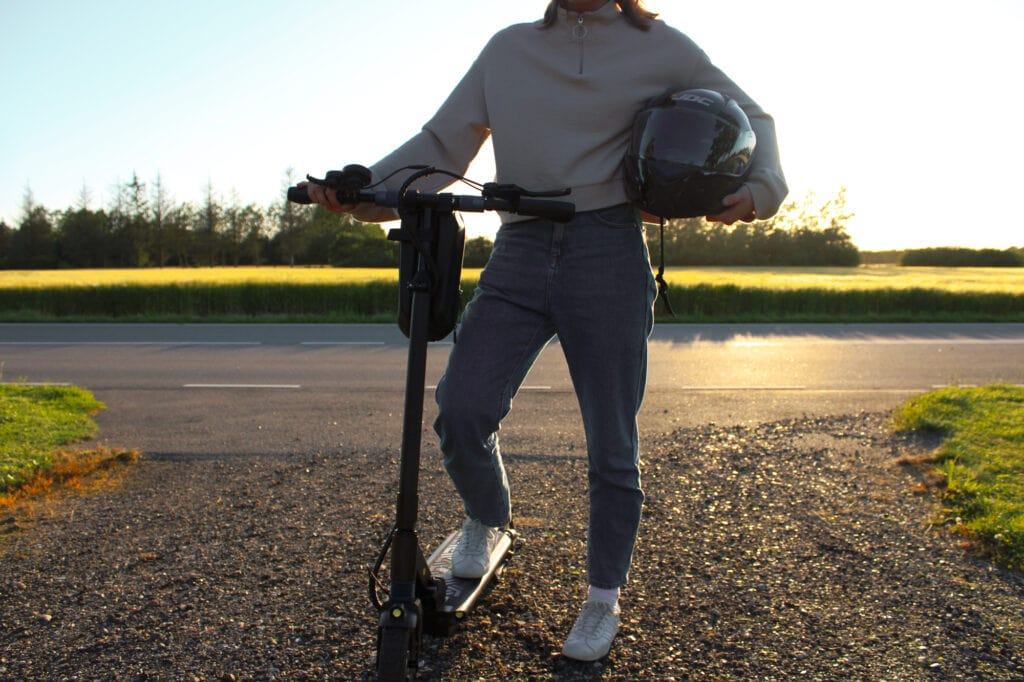 girl with her electric scooter helmet in the sunset