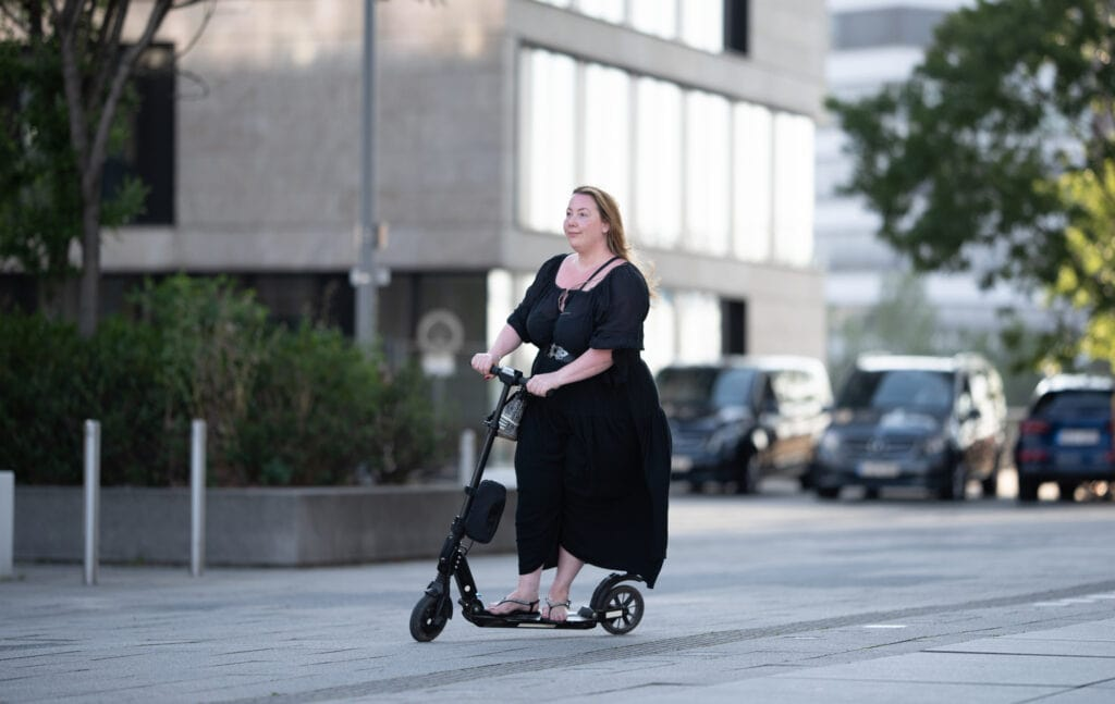 happy overweight woman riding on an electric scooter through the city