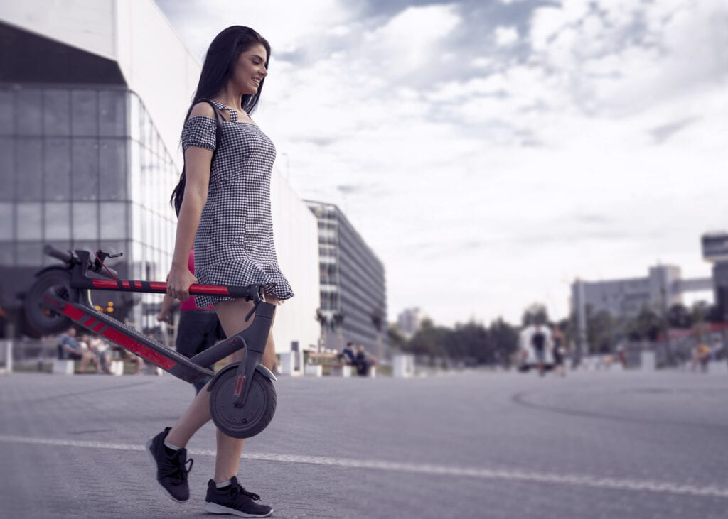 Cute girl carrying her folded e scooter on the street