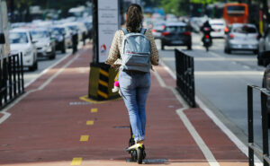 woman riding an electric scooter in the bike lane in the city