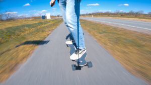 man riding a possway t2 electric skateboard on a bicycle path on a sunny day